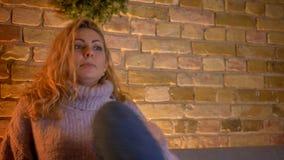Tiro do close up do filme de terror de observação fêmea louro caucasiano adulto e de obter da tevê um jumpscare na casa acolh video estoque