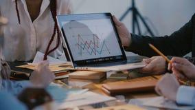Tiro do close-up, mãos masculinas do trabalhador de escritório que mostram o diagrama de mercado na tela do portátil na reunião m filme