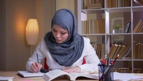 Tiro do close up do médico geral fêmea muçulmano adulto no hijab que estuda para um exame médico na biblioteca dentro video estoque