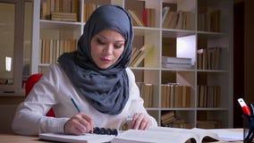 Tiro do close up do médico geral fêmea muçulmano adulto no hijab que estuda para um exame médico que toma o quando das notas video estoque