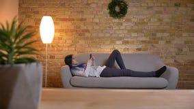 Tiro do close up do moderno caucasiano atrativo novo fêmea usando o telefone ao encontrar-se no sofá na casa acolhedor dentro filme