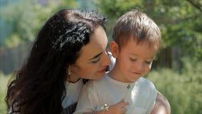 Tiro do close-up do movimento lento da mãe feliz que abraça sua criança e delicadamente de um despreocupado fundindo um ar livre  filme