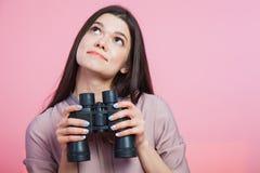 Tiro do close up, mulher que guarda vidros binoculares Imagens de Stock