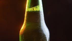 Tiro do close up do pescoço de brilho da garrafa de cerveja que gerencie ao redor no movimento video estoque