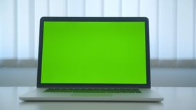 Tiro do close up do portátil com a tela chave do croma verde com a propaganda que coloca na tabela no escritório dentro video estoque