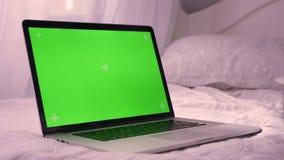 Tiro do close up do portátil com a tela verde da croma-chave que coloca na cama Propaganda na tela vídeos de arquivo