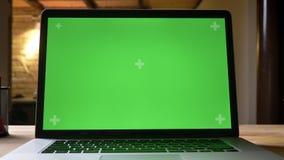 Tiro do close up do portátil com a tela verde com a propaganda nela na mesa no escritório dentro vídeos de arquivo