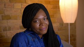 Tiro do close up do sorriso fêmea afro-americano adulto câmera alegremente de vista que senta-se no sofá dentro na vídeos de arquivo