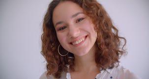 Tiro do close up do sorriso fêmea caucasiano encaracolado de cabelos compridos atrativo novo câmera alegremente de vista com