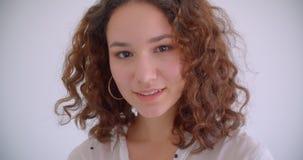 Tiro do close up do sorriso fêmea caucasiano encaracolado de cabelos compridos atrativo novo câmera felizmente de vista com fundo