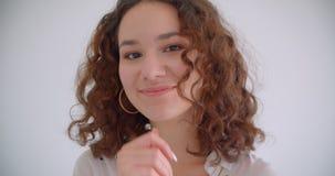 Tiro do close up do sorriso fêmea caucasiano encaracolado de cabelos compridos bonito novo felizmente levantando na frente da câm