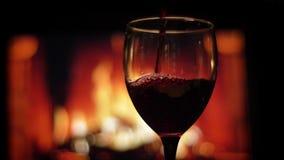 Tiro do close up do vinho tinto que está sendo derramado no vidro vazio com a chaminé morna acolhedor com as chamas no fundo vídeos de arquivo
