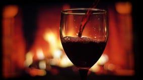 Tiro do close up do vinho tinto que está sendo derramado no vidro vazio luxuoso com a chaminé morna acolhedor no fundo dentro vídeos de arquivo