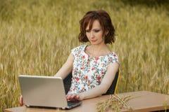 Tiro do conceito do negócio de uma jovem mulher bonita que senta-se em uma mesa usando um computador em um campo foto de stock royalty free