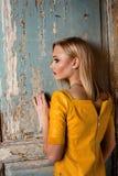 Tiro do estúdio da menina nova e bonita que está perto da porta velha no vestido de couro amarelo que veste no estúdio Menina lou Foto de Stock Royalty Free