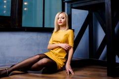 Tiro do estúdio da menina nova e bonita que senta-se perto da janela no vestido de couro amarelo que veste no estúdio Menina lour Imagem de Stock