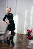 Tiro do estúdio da menina nova e bonita que stading no vestido preto que veste no estúdio Menina loura Fotografia de Stock Royalty Free