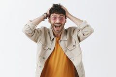 Tiro do estúdio do impresso homem de cabelo escuro atrativo excitado e entusiasmado em óculos de sol à moda com a barba que ofega fotos de stock royalty free