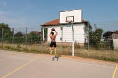 Tiro do jogador de basquetebol em um campo de jogos Fotografia de Stock Royalty Free
