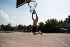 Tiro do jogador de basquetebol em um campo de jogos Fotos de Stock Royalty Free
