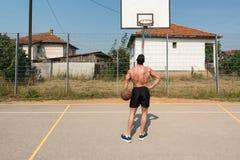 Tiro do jogador de basquetebol em um campo de jogos Fotografia de Stock