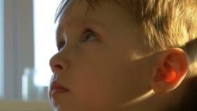 tiro do Lento-movimento da cara de um close-up pensativo da criança O menino olha pensativamente vídeos de arquivo