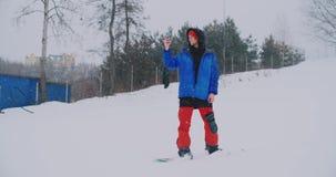 Tiro do movimento lento de um snowboarder que usa um smartphone ao conduzir em uma inclinação do esqui filme
