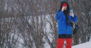 Tiro do movimento lento de um snowboarder que usa um smartphone ao conduzir em uma inclina??o do esqui vídeos de arquivo