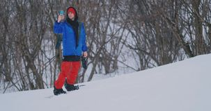 Tiro do movimento lento de um snowboarder que usa um smartphone ao conduzir em uma inclina??o do esqui video estoque