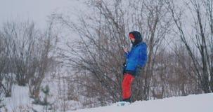 Tiro do movimento lento de um snowboarder que usa um smartphone ao conduzir em uma inclina??o do esqui filme