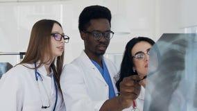 Tiro do retrato de três multi doutores nacionais que discutem o raio X dos pulmões do paciente durante o dia do trabalho vídeos de arquivo