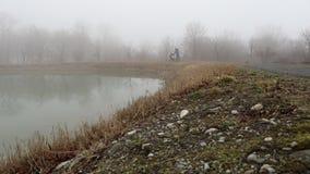 tiro do slider Banco vazio no parque perto da lagoa no dia nevoento, cena fria minimalistic da estação bench no lago na névoa nas filme