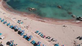 Tiro do zangão dos povos que encontram-se na praia Povos nos equipamentos nadadores que tomam o sunbath Meninas no biquini que de filme