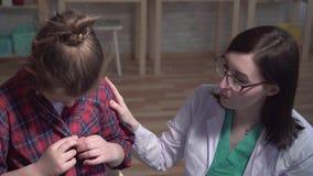 Tiro dramático de un niño enfermo y de un doctor en una capa blanca que hablan con un paciente de la clínica almacen de video