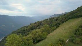Tiro em voo sobre as montanhas cobertas por árvores verdes com uma cidade no vale vídeos de arquivo