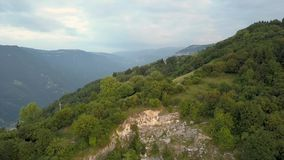 Tiro em voo sobre as montanhas cobertas por árvores verdes com uma cidade no vale filme