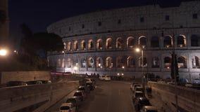 Tiro esquerda para a direita da bandeja de Timelapse do tráfego da noite próximo o Colosseo em Roma O Colosseum igualmente conhec filme