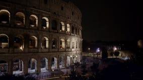 Tiro esquerda para a direita da bandeja do tempo real do tráfego da noite próximo o Colosseo em Roma O Colosseum igualmente conhe filme