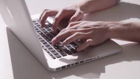 Tiro estático de um homem que datilografa no teclado de um portátil video estoque