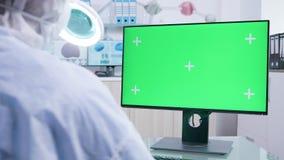 Tiro estático del personal de investigación en la bata blanca que mira el monitor aislado de la maqueta metrajes