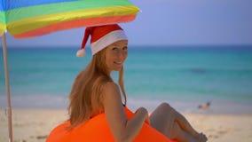 Tiro estupendo de la cámara lenta de una mujer joven en un sombrero de la Navidad que se relaja debajo de un paraguas en un sofá  almacen de video