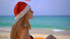 Tiro estupendo de la cámara lenta de una mujer joven en un sombrero de la Navidad que se relaja debajo de un paraguas en un sofá  almacen de metraje de vídeo