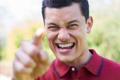 Tiro exterior da gritaria irritada e de apontar do homem novo na câmera fotos de stock royalty free