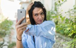 Tiro exterior da mulher caucasiano consideravelmente à moda para arranjar seu cabelo ao levantar para o autorretrato Foco seletiv fotos de stock royalty free
