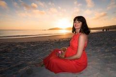 Tiro exterior da mulher gravida nova no vestido vermelho que senta-se na praia e que guarda o brinquedo do urso de peluche em sua Imagens de Stock