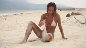 Tiro exterior da mulher 'sexy' nova bonita no roupa de banho, senta-se na praia no jogo com areia video estoque