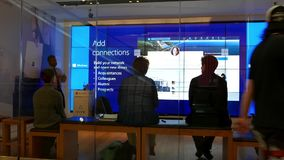 Tiro exterior de la gente que tiene una conferencia sobre cómo añadir la conexión de red en la tienda de Microsoft
