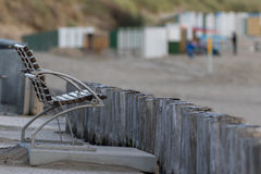 Tiro genérico de um banco e de cargos da madeira na praia Imagens de Stock