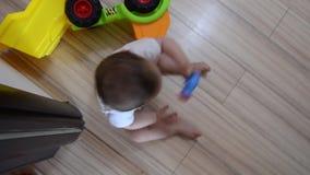 Tiro giratorio del alto ángulo, siete meses lindos del bebé que juega con los juguetes educativos en el piso metrajes