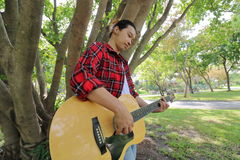 Tiro granangular del hombre joven hermoso que juega música en la guitarra acústica en un fondo hermoso de la naturaleza Fotos de archivo libres de regalías